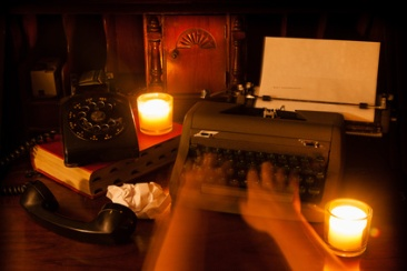 Ghost hands type on a vintage typewriter with candles, a book, and an old rotary phone